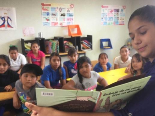 Feria del Libro en escuela de San Juan de los Planes - alumnos miran libro