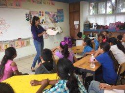 Mestra muestra libro en la Feria del Libro en escuela de San Juan de los Planes